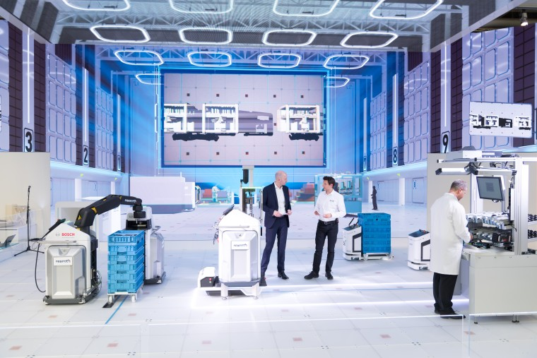 A futuristic-looking factory - one man in a white coat is operating a piece of machinery. Two men, one in a suit, one in a shirt, are standing further back talking.